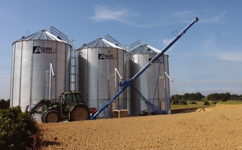 un tracteur avec vis sur chariot devant 3 silos à grain de stockage