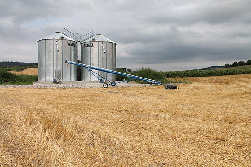 vis sur chariot dans un champs devant deux silos à grain a fond plat