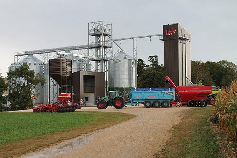 deux silos à grains fond plat un silo fond conique un boisseau et un séchoir LAW à économiseur d'énergie avec tracteur remorque transbordeur devant