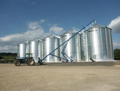 5 silos fond plat avec un tracteur entrainant une vis sur chariot