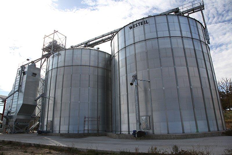 deux silos à grain a fond plat et un séchoir à maïs a colonne