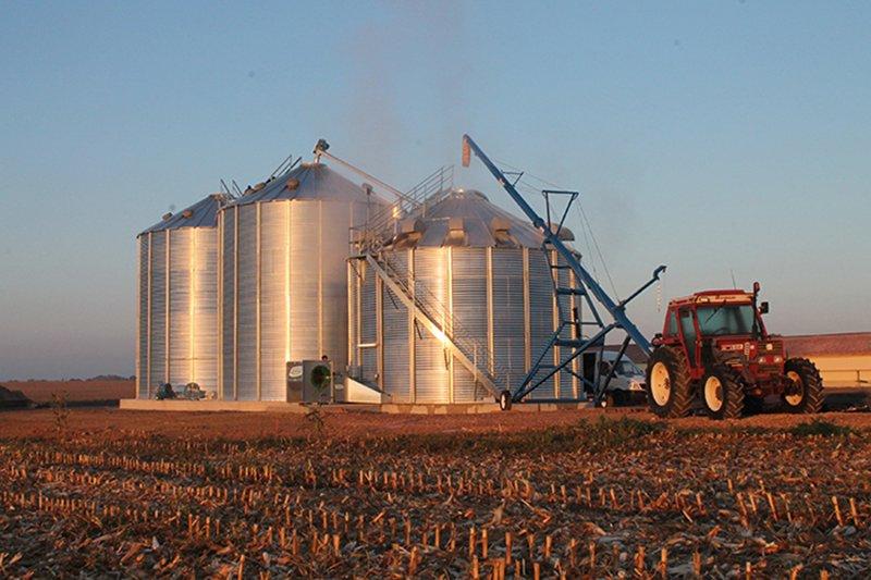 tracteur et vis à grain sur chariot chargeant une cellule sécheuse et deux silos de stockage au soleil couchant