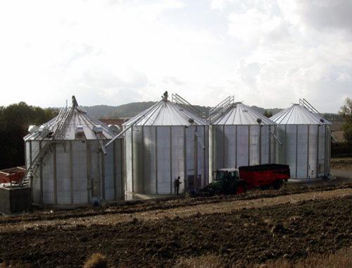 tracteur avec remorque devant trois silos à grain a fond plat et une cellule sécheuse