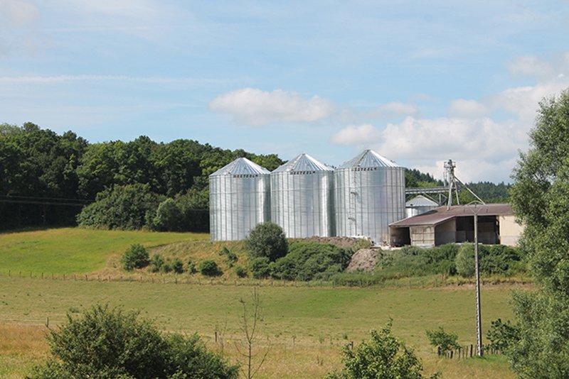 3 gros silos à grain a coté d'un bâtiment de stockage