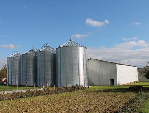 4 silos a grain alignés a coté d'un hangar de stockage