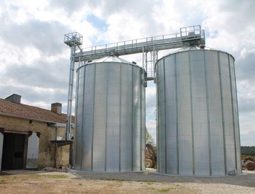 deux silos à grains avec élévateur à godet et passerelle supérieure