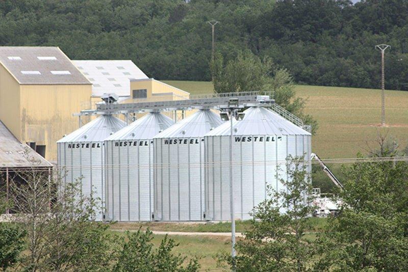 quatre silos fond plat à grain avec passerelle au dessus