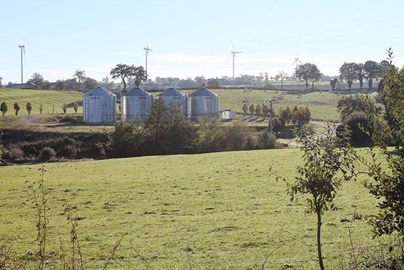 champs avec eoliennes et 4 silos a grains