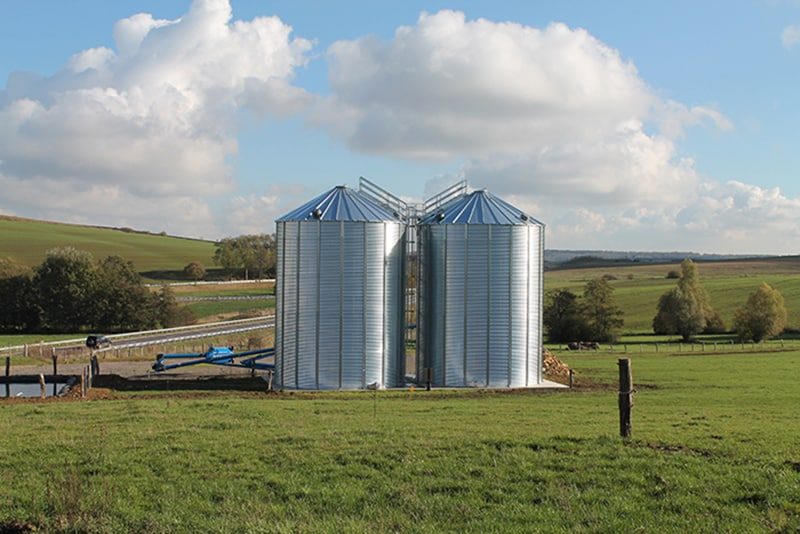 deux silos à grain fond plat au milieu d'un champ