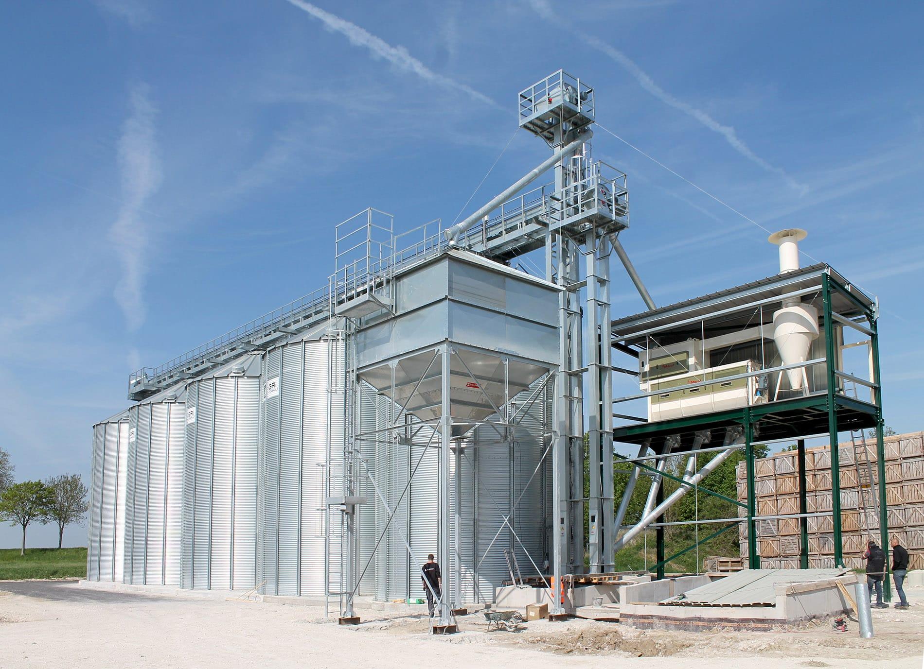 4 silos à grain alignés avec un boisseau des élévateurs à godets et un nettoyeur rotatif marot avec cyclone