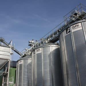 3 silos à grain agriconsult avec un convoyeur à chaine sur passerelle et un convoyeur incliné alimentant un boisseau